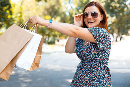 Happy red haired girl in sunglasses with shopping bags enjoying shopping