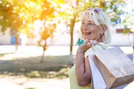 Beauty blonde smiling girl in sunglasses with shopping bags in the park on a sunny day. Shopping concept Imagens