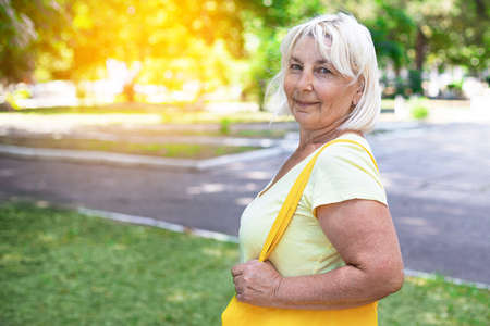 Adult blonde woman with yellow bag in park