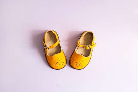 Bright yellow baby shoes on lilac background with copyspace. Baby clothes concept. Top view, flat lay Foto de archivo