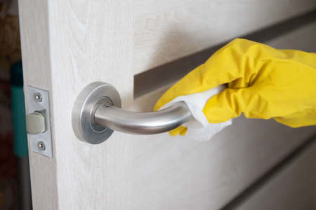 Coronavirus COVID-19 Woman hand wiping doorknob with antibacterial disinfecting wipe for killing corona virus on touching surfaces or touching public Banque d'images