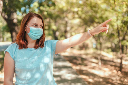 Coronavirus, covid 19. Caucasian european woman wearing a mask for prevent dust and infection virus hand shows direction in the city park or in public space
