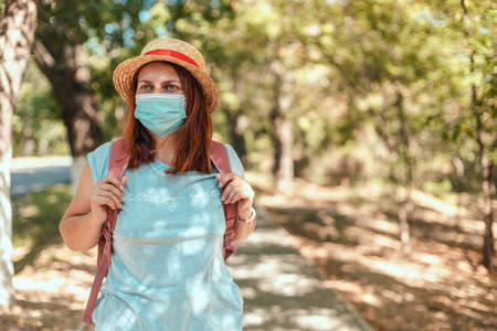 Tourist caucasian girl in summer straw hat and t-shirt with a backpack and a protective mask in a public place. Travel or vacation 2020 2021 concept
