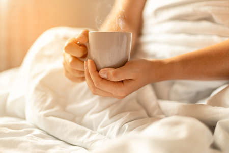 Woman hand holding cup of coffee or tea in bed on white blanket. Coffee morning concept Stock Photo