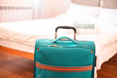 Blue travel suitcase in hotel room on summer vacation. Vacation and travel concept.