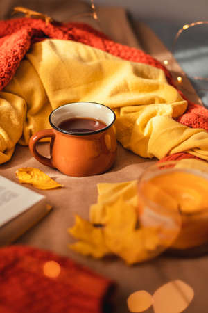 Hot cup of tea with autumn leaves and light garland decor on brown plaid in bed. Comfort and relaxation concept, vertical photo orientation