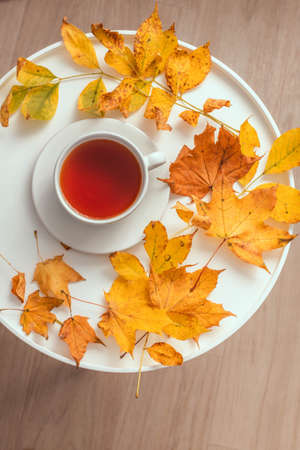 Cup of tea on wooden coffee table with yellow fall leaves. Comfort and relaxation concept, vertical photo orientation