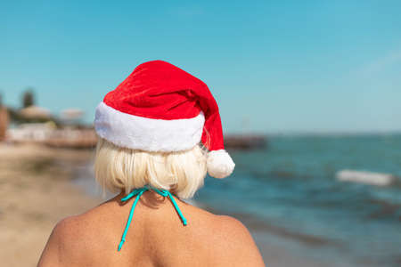 Woman in Santa Claus Hat sitting on sand of the beach. Christmas beach vacation travel banner