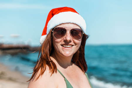 Young girl in santa hat, sunglasses and swimsuit smiling happy at camera on sea tropical ocean beach. Winter holidays or christmas celebration by the sea