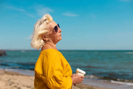 Adult woman in sunglasses and a yellow blouse with a paper cup of coffee to go by the sea on a sunny day. Coffee to go