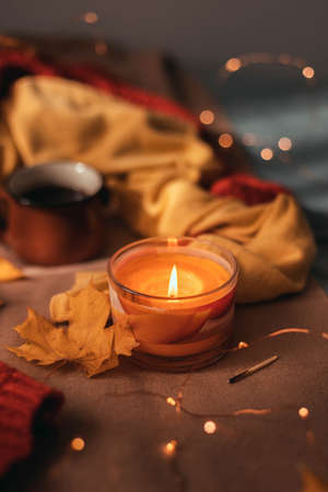 Burning aroma candle with autumn leaves and light garland decor on a brown plaid in bed. Autumn style. Hygge concept, vertical photo orientation