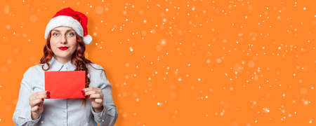 Beautiful caucasian young girl in santa hat with red envelope blank mockup on orange background. Panoramic banner with free space for text