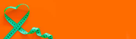 Green metric measuring tape on horizontal orange background. Loving yourself healthy body concept 版權商用圖片