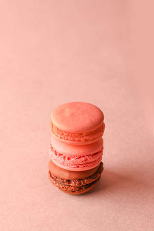 Pink and brown french dessert macaroons on a pastel pink background with copyspace, side view, vertical orientation