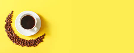Hot cup of coffee and coffee beans on minimal yellow horizontal background, top view