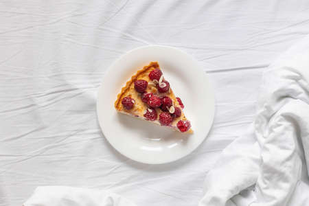 Flat lay piece of classic cheesecake with raspberry berries on a white plate on the bed. Homemade healthy natural summer dessert cake.