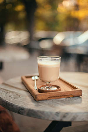 Latte or coffee with milk drink on a wooden tray on a street table in the park. Morning coffee on the terrace in cafe 版權商用圖片