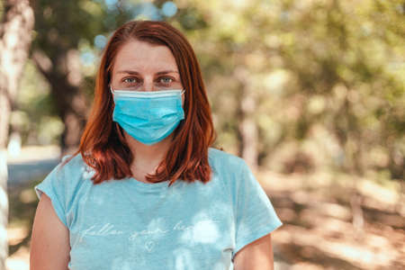 Coronavirus, covid 19. Caucasian european woman wearing a mask for prevent dust and infection virus in the city park or in public space