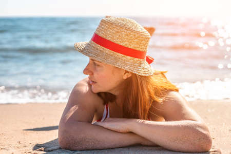 Tanning young girl in a hat and swimsuit lies on the beach. Summer holiday fashion concept 版權商用圖片
