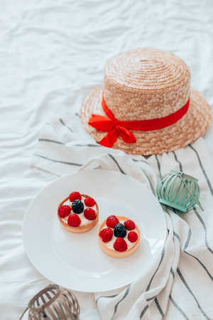 Delicious raspberry tartlets with meringue on a white plate. Straw hat and cotton towel dress on white bed