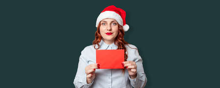 Portrait of cheerful girl in a santa hat holding a red wishlist letter mockup on dark green wall background. New year celebration banner, copy space.