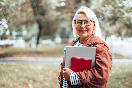 Adult caucasian blonde teacher woman in glasses for sight with books, notebook and magazines looking at the camera in the park