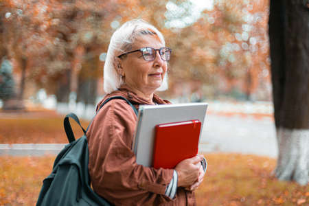 Adult caucasian blonde teacher woman in casual clothes stands holding notebooks and backpack walking in the autumn park. University, learning education concept. Copy space. 版權商用圖片