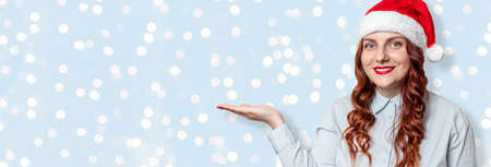 Caucasian cheerful woman in santa hat with her hand palm pointing on light blue banner with copy space. 版權商用圖片 - 158155869