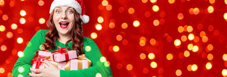 Caucasian cheerful woman in a santa hat with christmas gift box. New year celebration banner, copy space. Surprising giftbox in dating on end year party. 版權商用圖片 - 158156123