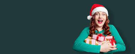 Portrait of pretty santa hat woman holding gift boxes for holiday over green background. Wow celebrating New Year web banner 版權商用圖片 - 158175150