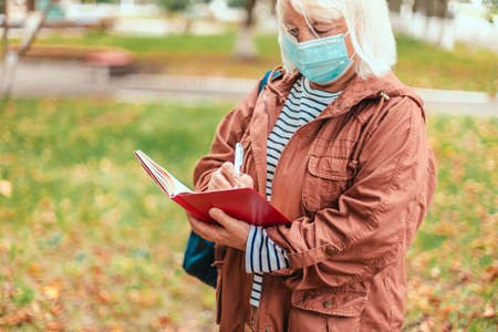 Adult caucasian blonde woman in casual clothes and protective mask stands taking notes into notebook using pencil at a park 版權商用圖片 - 158175738
