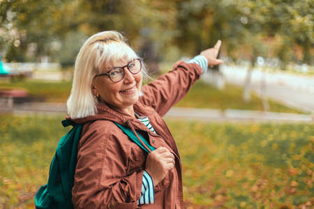 Adult blond woman in comfortable clothes with a backpack shows the direction in the park with her finger. Tourist traveler in a beautiful place