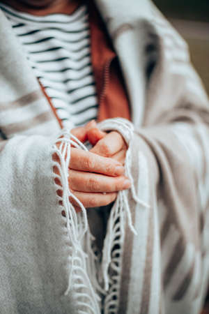 Female hands in a warm knitted blanket to keep warm in cold October weather and standing in the forest or park