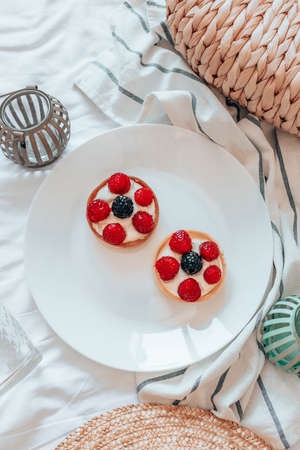 Delicious raspberry tartlets with cream filling on white plate. Fresh fruit tart on white background. Flat lay and copy space. Top view. Vertical photo orientation 版權商用圖片 - 158155912