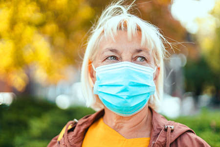 Caucasian adult blond woman 50 years old in bright robe and protective medical respirator mask looking away on the park