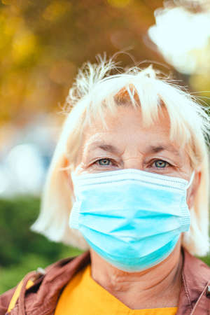 Coronavirus, covid 19 concept. Portrait of adult blonde woman of about 50 in a medical protective mask looking at the camera. Vertical photo orientation 版權商用圖片 - 158175741