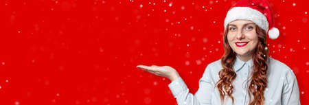 Cheerful santa hat woman standing pointing empty hand palm on light red banner with copy space. 版權商用圖片