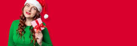 Cheerful santa hat woman holding gift box with red bow, pointing look at the camera over red background 版權商用圖片 - 158308607