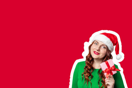 Santa hat woman holding gift box with red bow, pointing look at the camera over red background
