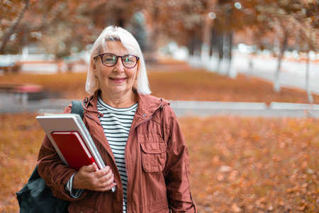 Smiling adult woman in casual clothes stands holding notebooks and backpack walking in the autumn park