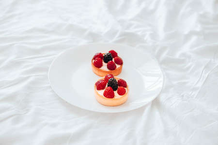 Raspberry tartlets with cheese creme, fresh berries on white plate. Fresh fruit tart on white background