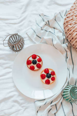 Delicious raspberry tartlets with cream filling on white plate in the bed. Fresh fruit tart on white background 版權商用圖片