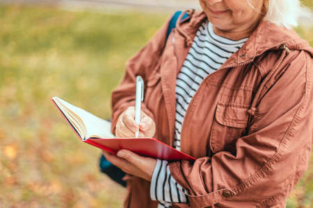 Woman hand take notes with a pen on a notebook in garden or park 版權商用圖片 - 158379131