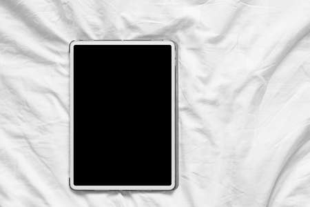 Top view mockup of white tablet pc with blank desktop white screen on a cozy white bed at home 版權商用圖片