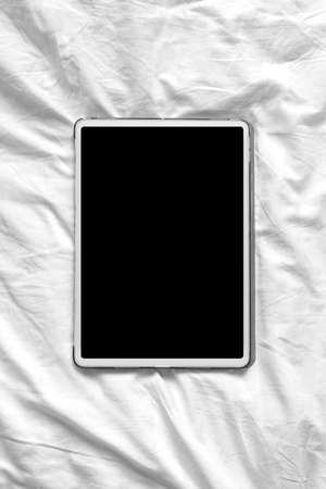 Top view mockup image of blank screen tablet on a cozy white bed at home. Vertical photo orientation