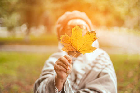 Portrait of girl with yellow autumn leaf in a sunny autumn park. Happy caucasian blonde woman under warm knitted blanket walking in autumn park.