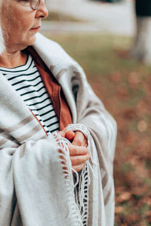 Fall vertical photo of a woman wrapped in a cozy woolen blanket walking in an autumn forest