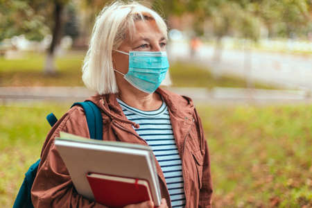 Outdoor autumn portrait of blonde woman wearing protective medical mask, casual clothes, glasses and a backpack holding an exercise book, notebook walking in street