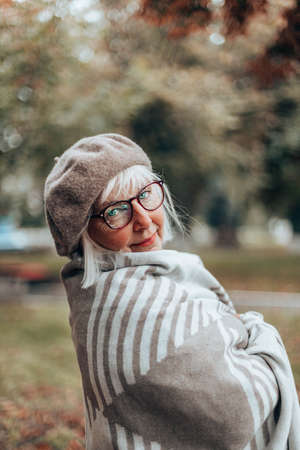 Happy caucasian lady in stylish beret,glasses, cozy blanket walk on a windy day in autumn or fall