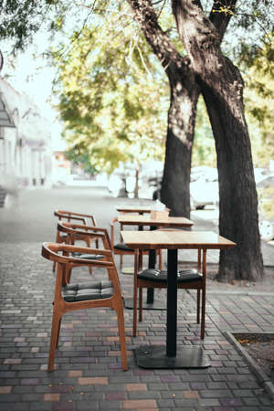 Outdoor empty street restaurant with wood stile chairs. Coronavirus crisis 版權商用圖片 - 158379241
